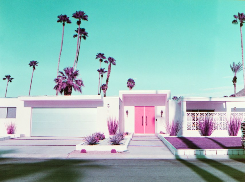 A single story house with palm trees in the background, and a green sky