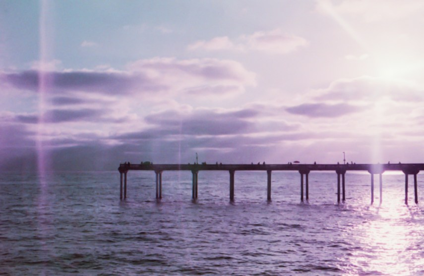 a pier jutting out into the ocean with a purple tinged sky