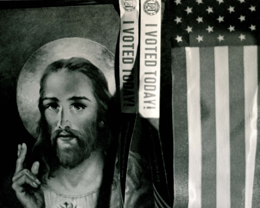 a picture of jesus next to a USA flag with i voted today strips hanging down