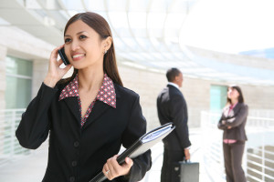 A pretty asian business woman on cell phone with co-workers in background