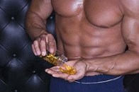 Muscular man pouring pills into hand