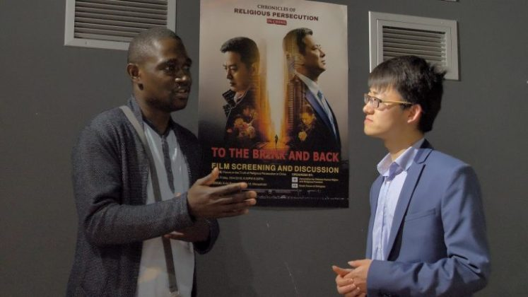 Mr. Totow Jean-Didier from Congolese Community in Greece exchanges views with a member of ACHRRF on the film To the Brink and Back. (Photo: Zhou Lei)