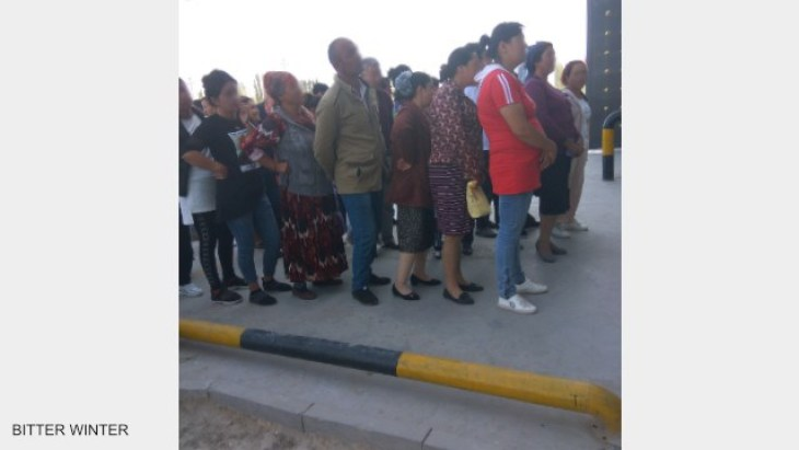 The detainees' family members who are attending the public trial meeting line up outside the transformation through education camp, waiting to be summoned.