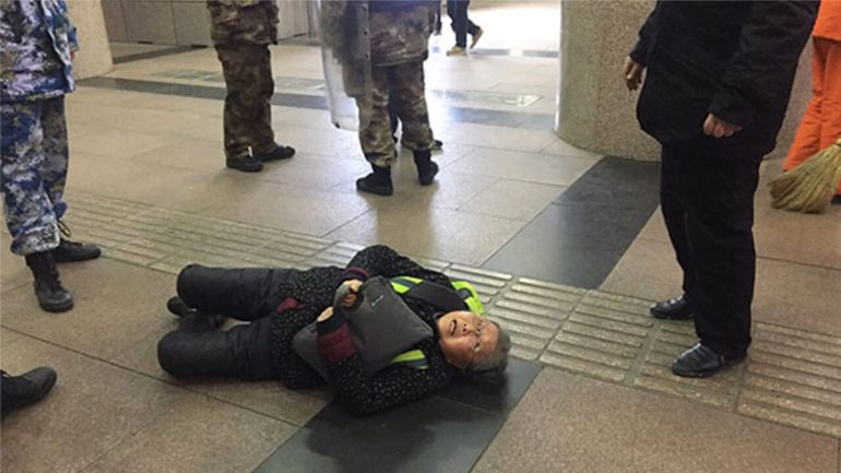 Pu Wenqing, the elderly mother of Chinese rights activist and website editor Huang Qi, after she was shoved to the ground by official 'interceptors' in Beijing, who detained her after she tried to appeal for Huang's release, Dec. 7, 2018.