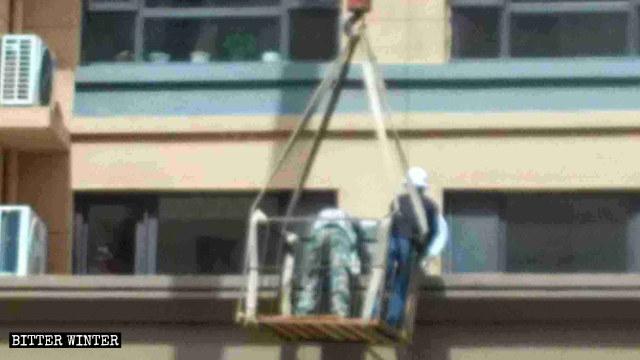 Workers dismantling satellite antennas