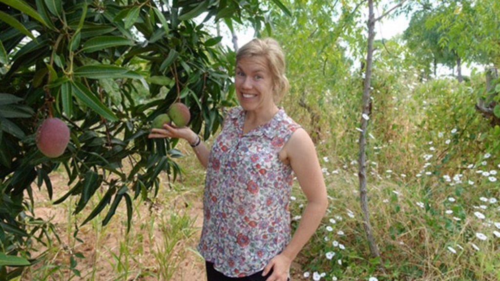 Malin, en av våra kunder framför ett Mango-träd på Simon Mullis gård