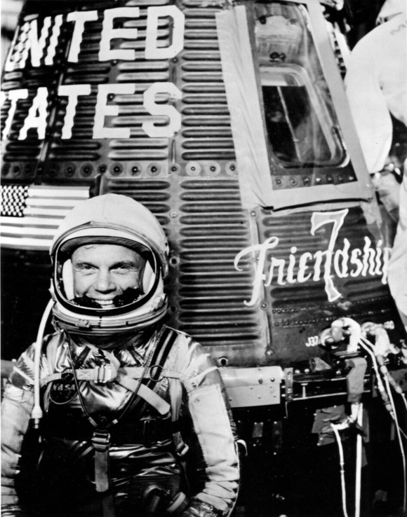 Smiling man in space suit standing next to a one-person space capsule.