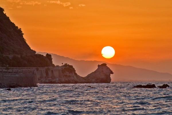 Rocky Shoreline, die Sonne ein gelb-weißer Kreis über großen spitzen Felsen gegen orangefarbenen Himmel.