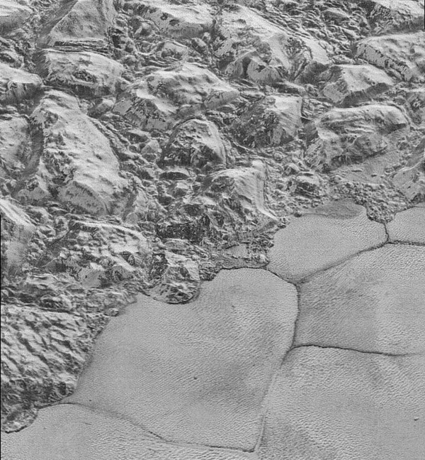 View larger. | NASA calls this image 'the mountainous shoreline of Sputnik Planum.' It's not a shoreline as on Earth, of course; it's a place where two kinds of ice meet. The mountainous region - informally named al-Idrisi mountains - is made of great blocks of Pluto's water-ice crust. Some stand as much as 1.5 miles high. The mountains end abruptly at the shoreline of the informally named Sputnik Planum, where the soft, nitrogen-rich ices of the plain form a nearly level surface.