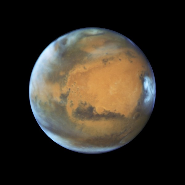 View larger. | This image shows our neighbouring planet Mars, as it was observed shortly before opposition in 2016 by the NASA/ESA Hubble Space Telescope. Some prominent features of the planet are clearly visible: the ancient and inactive shield volcano Syrtis Major; the bright and oval Hellas Planitia basin; the heavily eroded Arabia Terra in the centre of the image; the dark features of Sinus Sabaeous and Sinus Meridiani along the equator; and the small southern polar cap. Image via NASA, ESA, Hubble Heritage Team, J. Bell, M. Wolff.