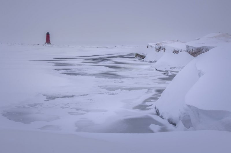 Frozen waves, lighthouse in the background, glacial cliffs on the right.