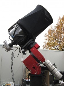 Short, thick telescope with wires trailing from it, standing on mounting outdoors.