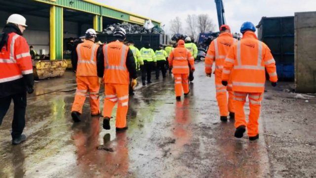 Members of Network rail in visibility jackets walk away in a group.