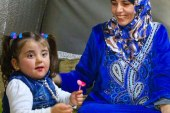 Syrian mother nurtures an orphaned girl in an IDP camp in rural Idlib