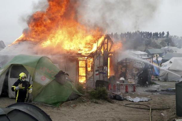 """Firefighters extinguish burning makeshift shelters and tents in the """"Jungle"""" on the third day of the evacuation of migrants and their transfer to reception centers in France, as part of the dismantlement of the camp in Calais"""