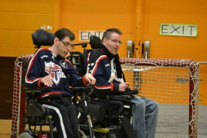 Two power wheelchair hockey players, one goaltender in front of the net and a defenseman