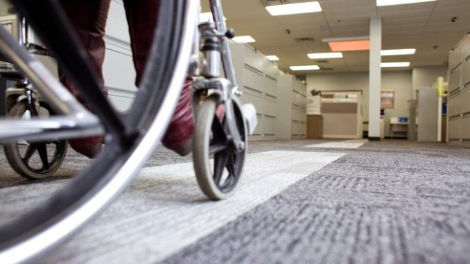 Photo of the wheels of a wheelchair moving down a office hallway
