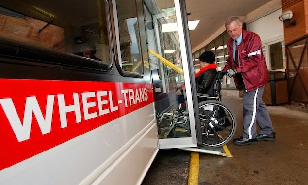 Photo of TTC Wheeltrans driver helping a customer up the ramp onto the bus