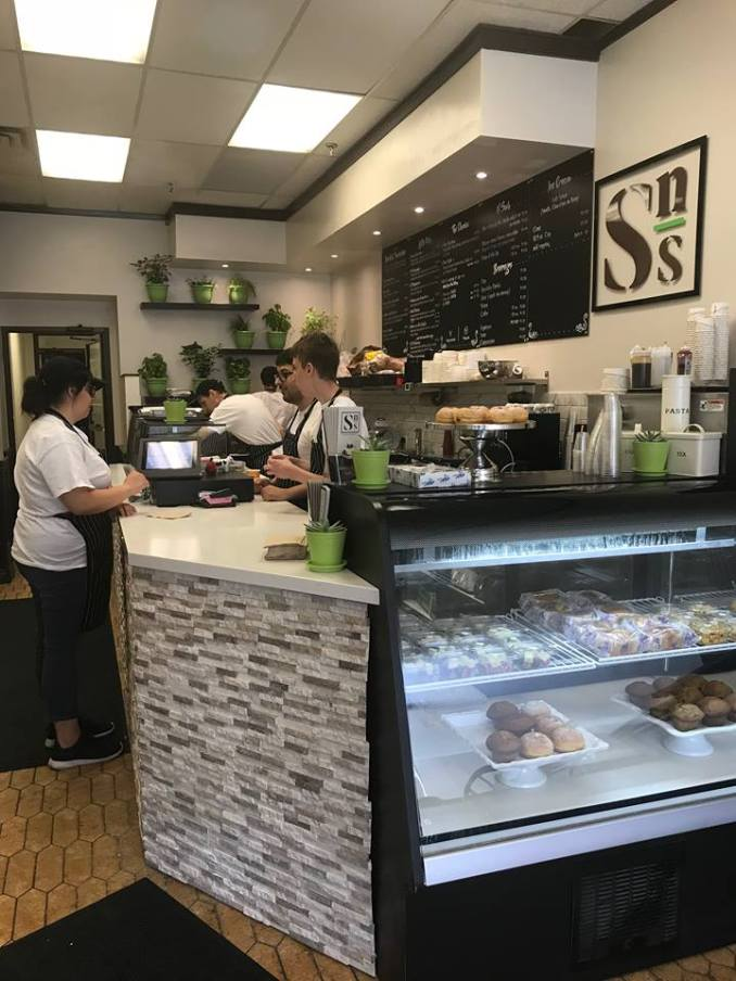 Photo of the inside of restaurant Sandwich n' Such. Main counter and fridge displaying pastries, and four employees behind the counter and another in front of the counter talking.