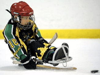 Photo of a boy in full gear with helmet and sticks playing sledge hockey on ice.