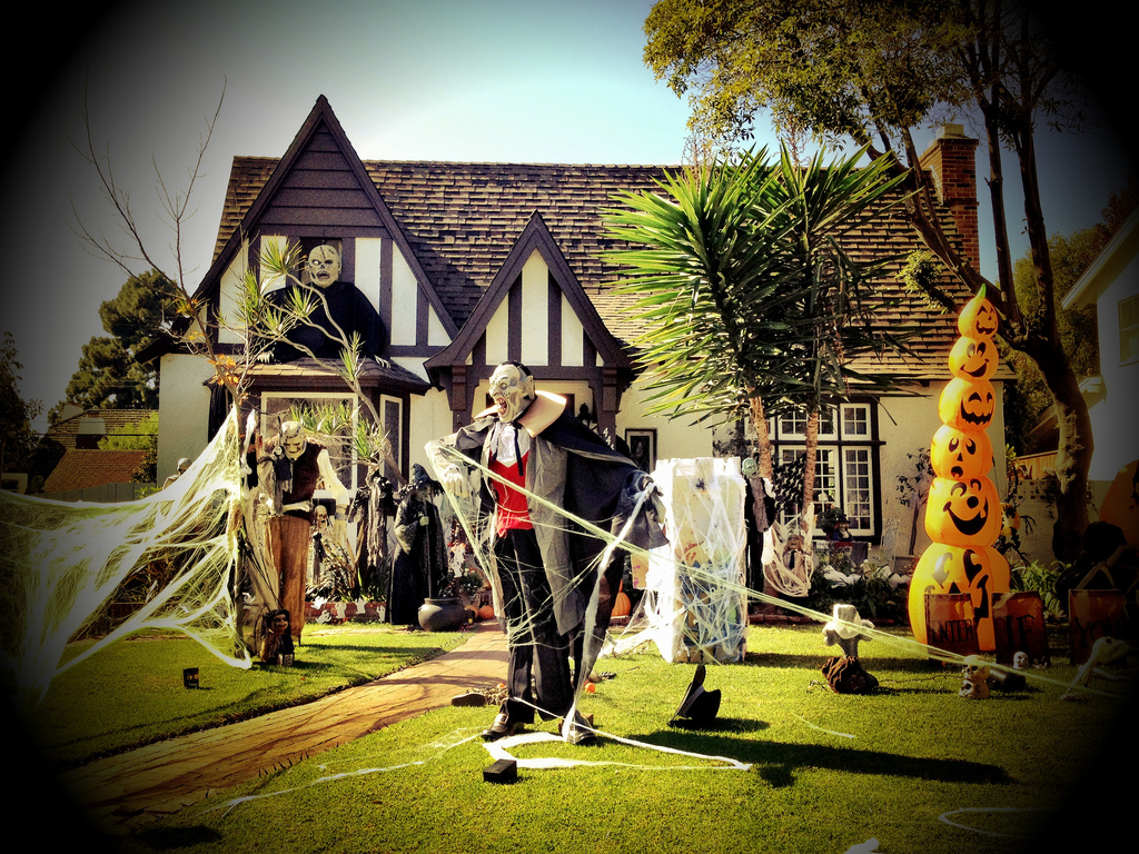 Photo of the front of a home decorated for Halloween with a vampire, inflated stack of pumpkin and cobwebs