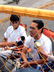 Ariel Varela speaks from behind the police barricade at the start of the Indignado hunger strike