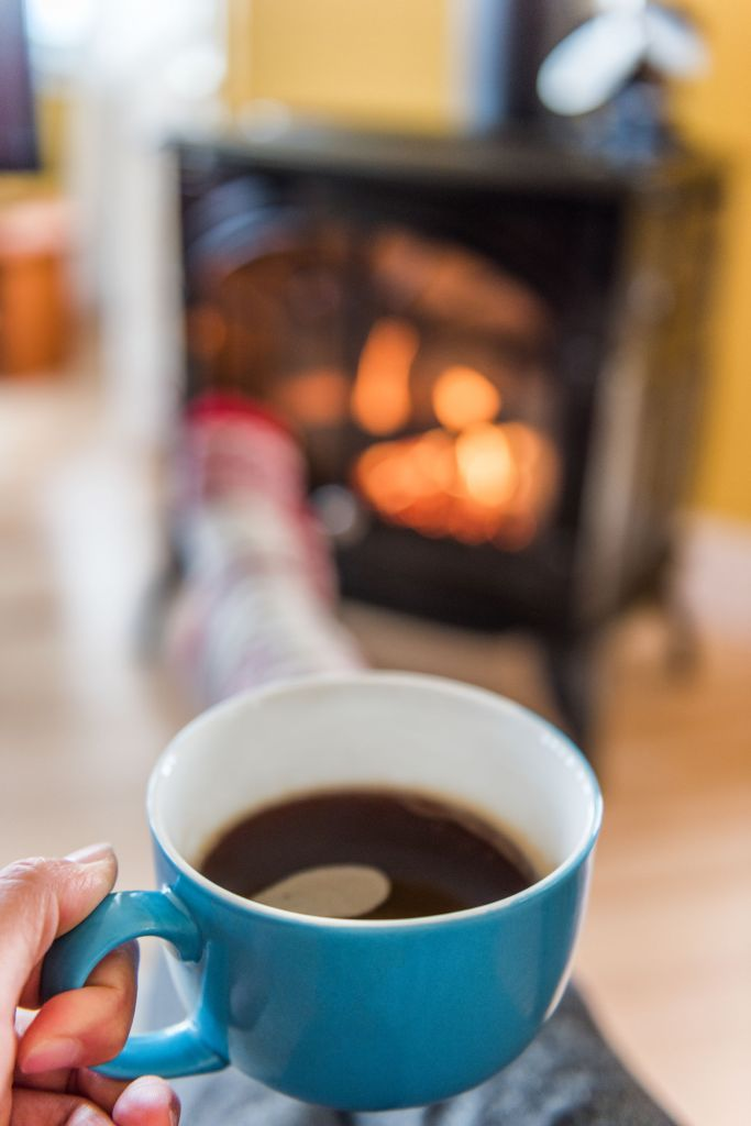 Cozy autumn lifestyle woman drinking coffee relaxing by fireplace at home. Cold winter or fall season. House heating comfort interior.