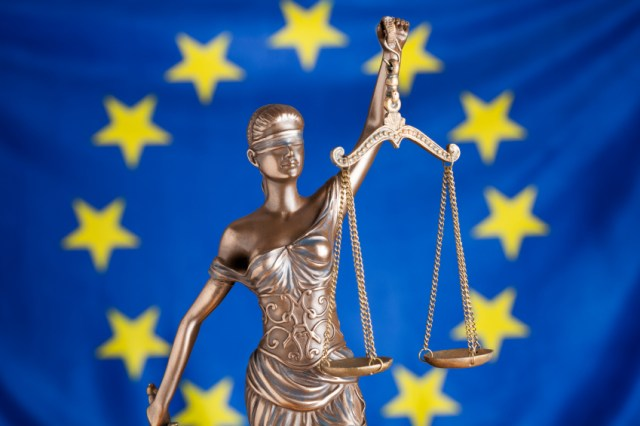 Studio shot of Lady of Justice statuette against European Union flag