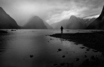 photo of person standing near the water looking at gray mist