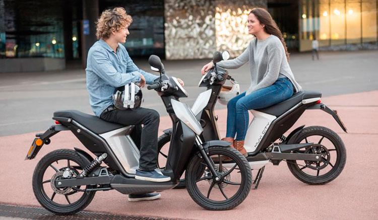 Imagen donde podemos ver dos scooters Torrot Muvi, en visión lateral, uno conducida por un chico y la otra por una chica.