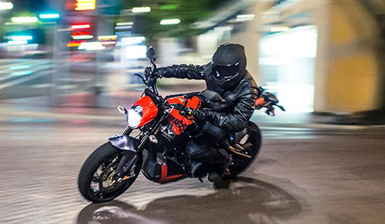 Imagen donde vemos la Victory Empulse TT tomando una curva en medio de la noche en una ciudad.