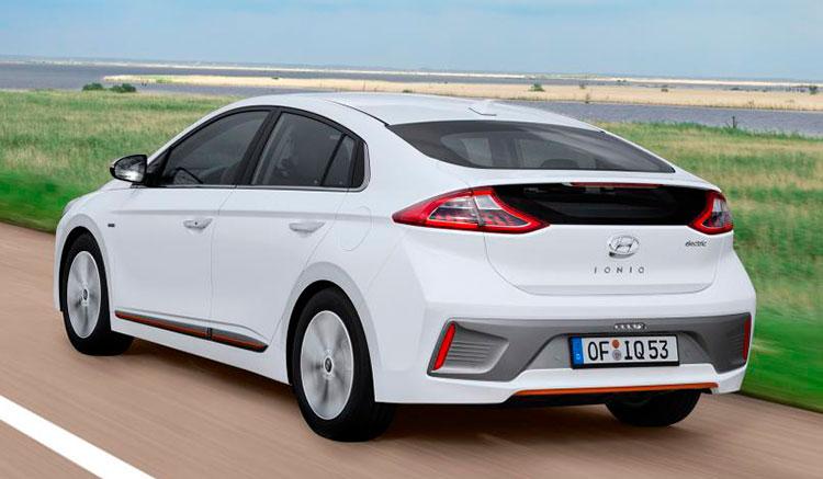 Imagen donde vemos un Hyundai Ioniq Electric circulando por una carretera, con un verde prado de fondo.