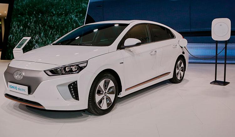 Imagen donde vemos un Hyundai Ioniq Electric de color blanco en una exposición, recargando sus baterías.