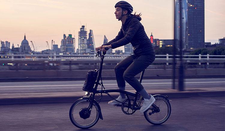 Imagen donde podemos ver una chica circulando con una Brompton Electric por ciudad, durante el atardecer.