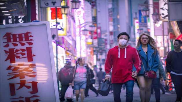 Un hombre con una mascarilla puesta en una ciudad asiática.