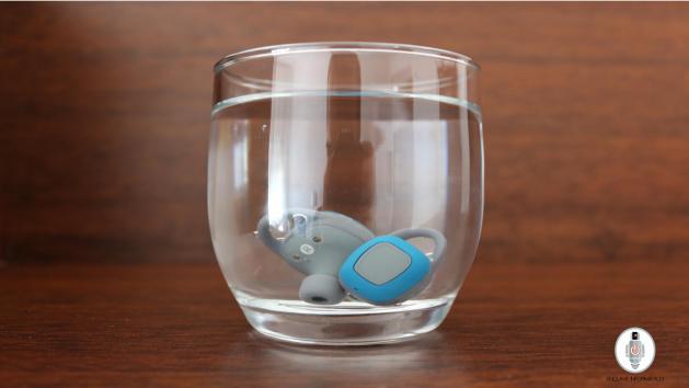 Auriculares dentro de un vaso lleno de agua.