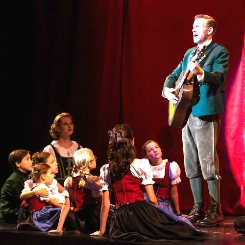 """Ben Davis as Captain von Trapp sings """"Edelweiss,"""" surrounded by Maria and the children."""