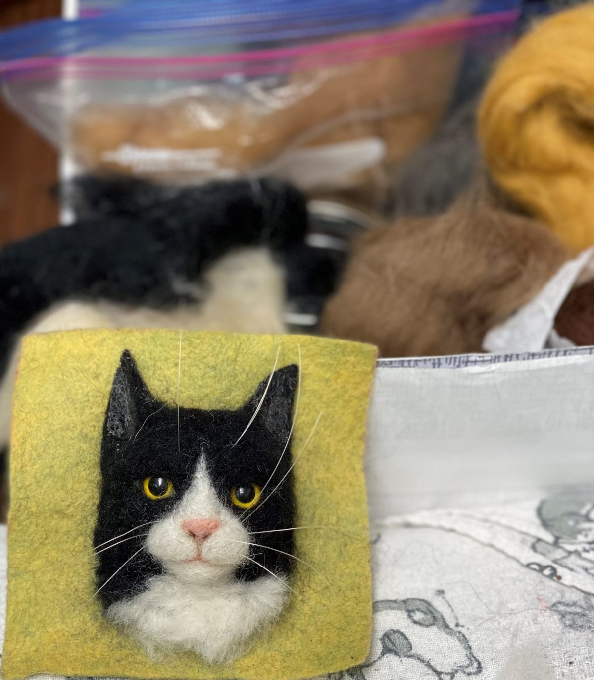 A 3D portrait of a black-and-white tuxedo cat head, created by needle felting, sits on a light green background. Behind the portrait are a variety of needle felting materials and fibers.