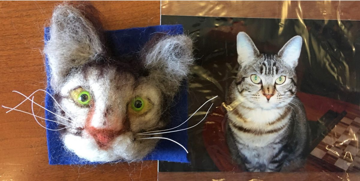 A 3D needle-felted portrait of a grey tabby cat sits next to a photo of the real cat.