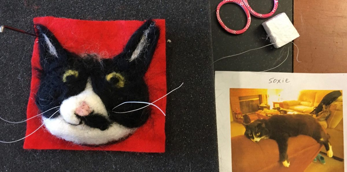 A 3D, needle-felted portrait of a black-and-white tuxedo cat's head sits next to a photo of the actual cat. In the photo, the cat is splayed out on the back of a sofa. The cat's name is Soxie.