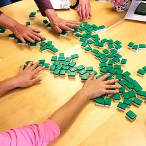 hands shuffling mahjong tiles