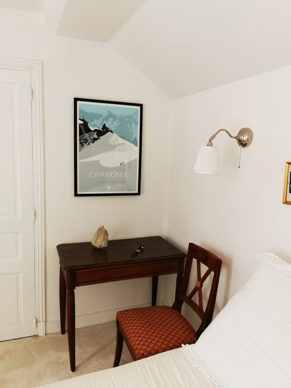 L'affiche 50x70 de Chamonix accrochée au mur dans un cadre noir en décoration d'une chambre parentale