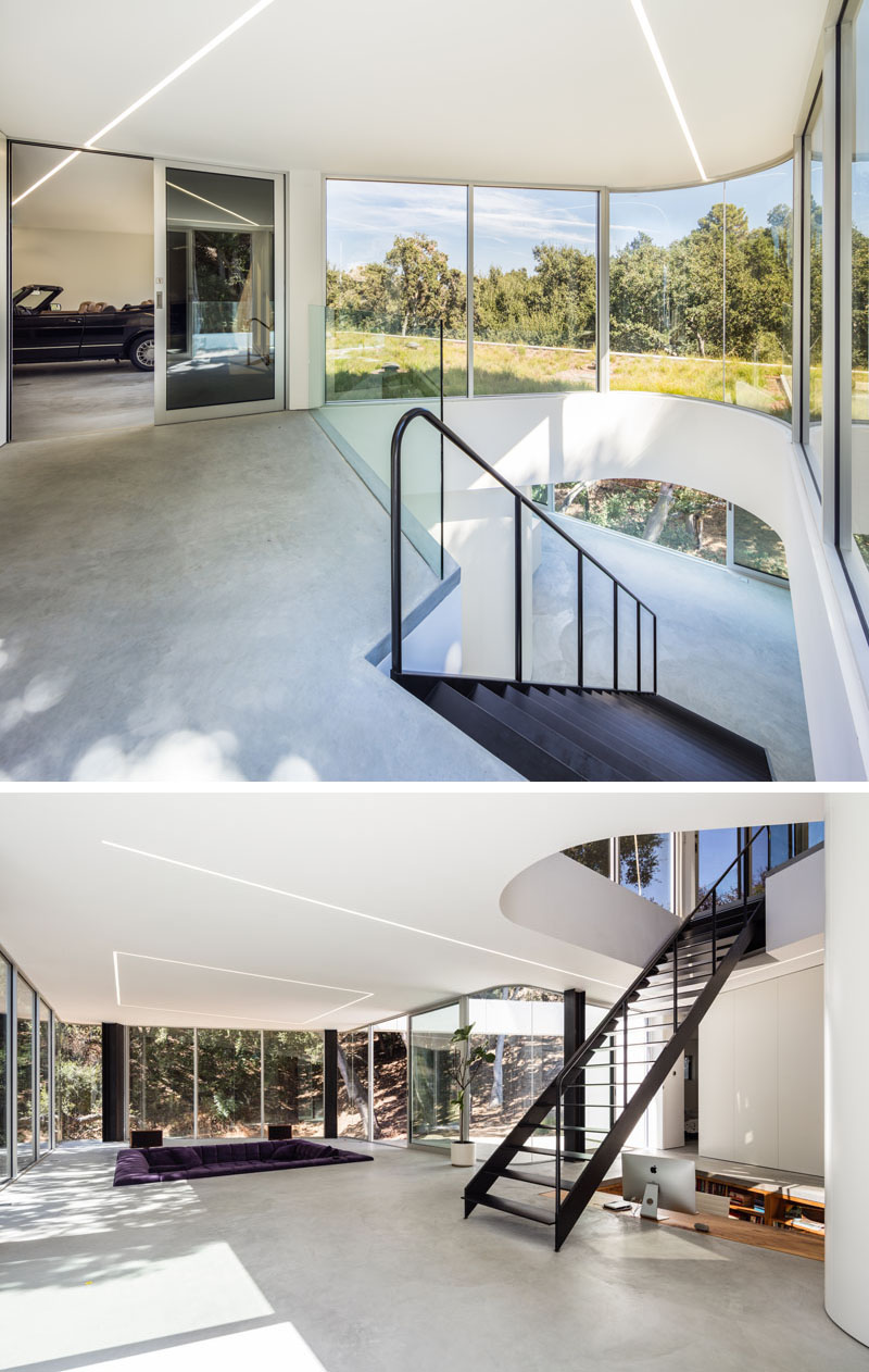 Next to the garage in this modern house, are stairs that lead down to the living level of the house, and sunlight from the curved windows is able to funnel down through the stairwell. #BlackStairs #CurvedWindow