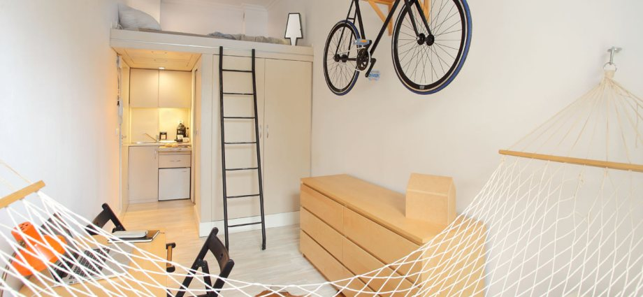 Interior of a micro apartment with a bike and a bike rack and a ladder to a bed