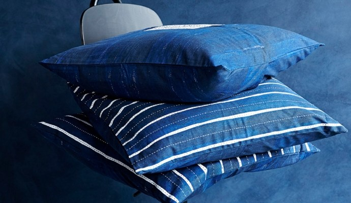 Three blue handmade homeware cushions stacked on top of each other