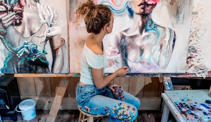 Young female artist sitting while painting