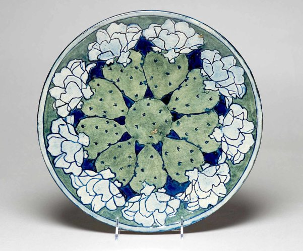 A plate with a border of flowering cactus, from about 1903, in an exhibition at Tulane.Credit...Owen Murphy