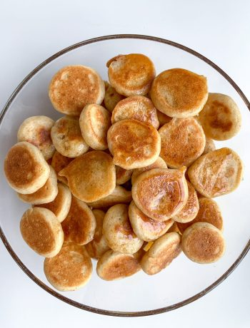 Mini pancake cereal in a bowl with maple syrup