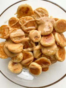 Mini pancake cereal in a bowl with peanut butter
