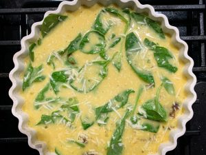 Crustless quiche with spinach, asiago, and french onion spread before it goes into the oven